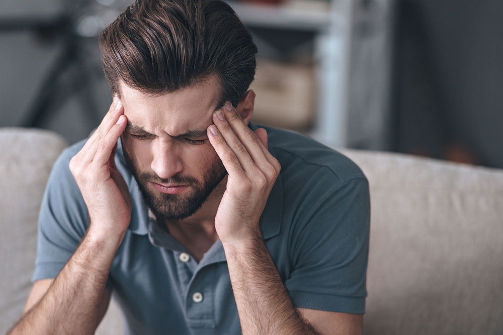 Man with a headache needs to seek chiropractic care in Puyallup.